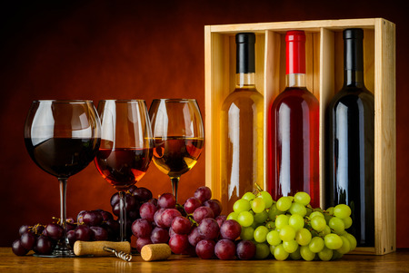 Three glasses and bottles of wine. White, red, and rose wine. Stock Photo