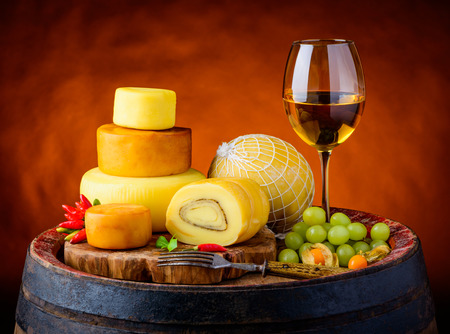 Glass of white wine with cheese wheele, smoked cheese and truckle cheese in vintage still life