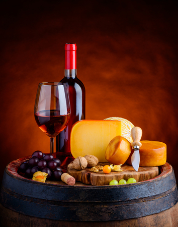 hard cheese: Rose wine in glass and bottle with grapes and gouda hard cheese and smoked cheese wheel on wooden barrel Stock Photo