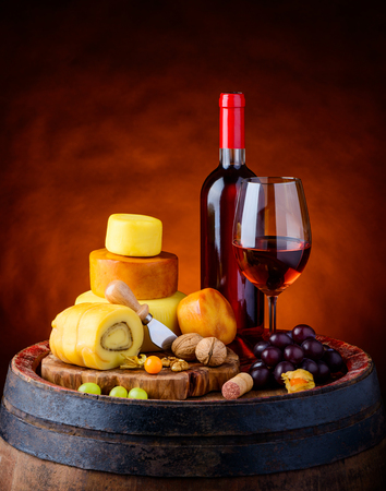 wheel barrel: Cheese Wheel  and smoked cheese with bottle and glass of rose wine on wooden barrel Stock Photo