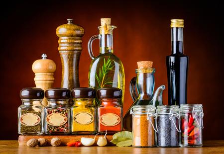 Diversi bicchieri e bottiglie di condimento alimentare e spezie in vita ancora