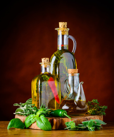 extra virgin: tree Bottles of extra virgin olive oil with pepper greef food herbs and rosemary Stock Photo