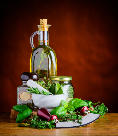 Extra virgin olive oil in bottle and green herbs with herbs chopper and pestle and mortar in still life
