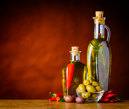 olive oil bottle: Dark and light olives with two bottles of extra virgin olive oil and pepper with copy space