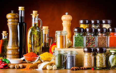 Bottles of oil and Balsamic vinegar and different spices and seeds and cooking ingredients