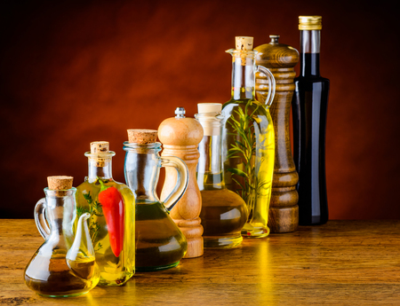 Bottles of cooking oil and winegar with salt and pepper mill grinder