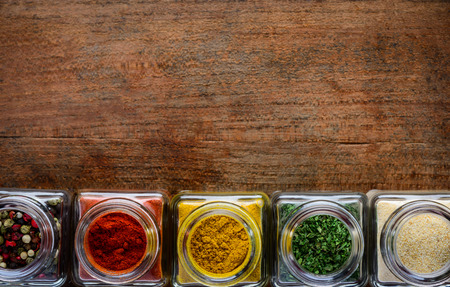 curry powder: Pepper, curry powder, thyme food spices in glass jars with copy space Stock Photo