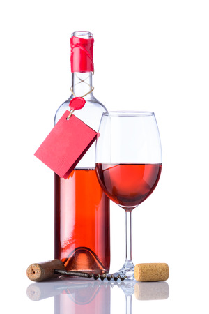 Opened bottle rose wine with label and wineglass with cork and corkscrew isolated on white background Stock Photo