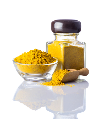 curry powder: Yellow curry powder in glass jar isolated on white background