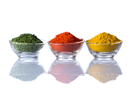 curry powder: Green Dried Herbs in glass Jar and Paprika powder and curry powder isolated on white background