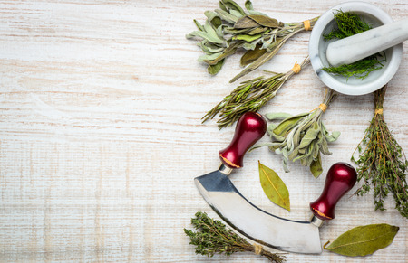 bay leaf: Cooking Herbs and pestle and mortar with herb chopper mezzaluna. The herbs are Sage, thyme, dill, bay leaf and rosemary