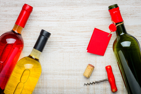 cork screw: tree bottles of wine, one open, one rose and a white wine with cork and cork screw
