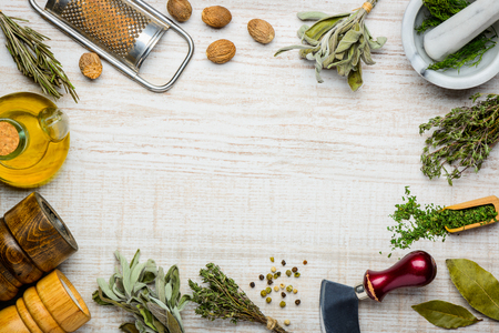 Cooking Ingredients and herbs as frame. Sage, rosemary seasoning and kitchen utensils copy space