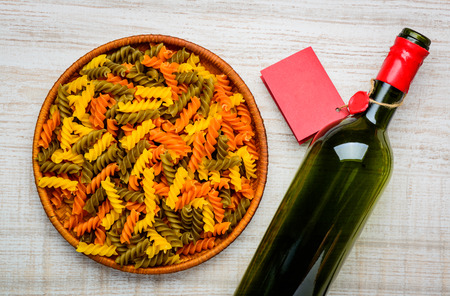 colored bottle: Top View of Colored Fusilli Doppia Rigatura pasta and bottle wine with red label Stock Photo