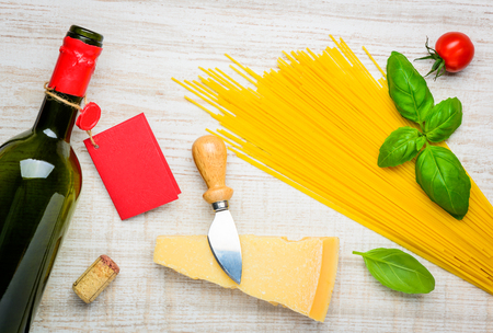 bootle: Bottle of Wine with red label, Parmigiano reggiano parmesan hard cheese with yellow spaghetti pasta. Italian cuisine. Stock Photo
