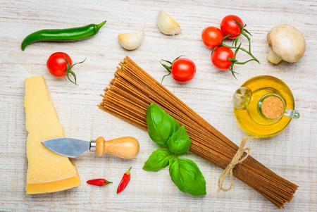 hard cheese: Italian Food, brown Spaghetti Pasta with Parmigiano Reggiano Parmesan Hard Cheese and cooking ingredients, oil, herbs and seasoning Stock Photo