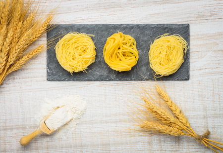 yellow flour: Italian Food, yellow Tagliatelle or Tagliolini Pasta with wheat and Flour Stock Photo
