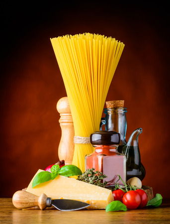 vegtables: Italian Cuisine cooking ingredients with yellow Spaghetti, Parmigian Reggiano Parmesan cheese and spices with Seasoning and Vegtables
