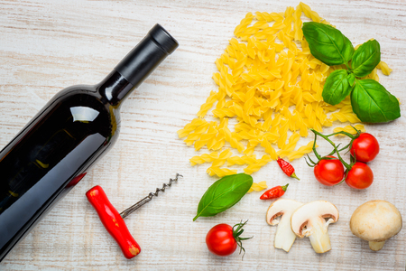 vegtables: Bottle of red wine with corkscrew and Fusilli doppia rigatura Pasta and fresh vegtables