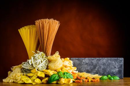 Pasta italiana con copia espacio. Cocina italiana con espagueti, tagliatelle, tortelini y fusilli doppia rigatura Foto de archivo