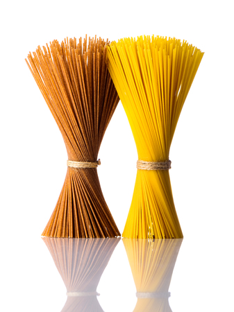 bundles: two bundles of spaghetti pasta, brown and yellow, isolated on white background. Italian or mediterranean cuisine