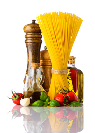 mediterranean cuisine: Yellow Spaghetti with seasoning, vegetables and spices on white background. Italian and Mediterranean cuisine food.