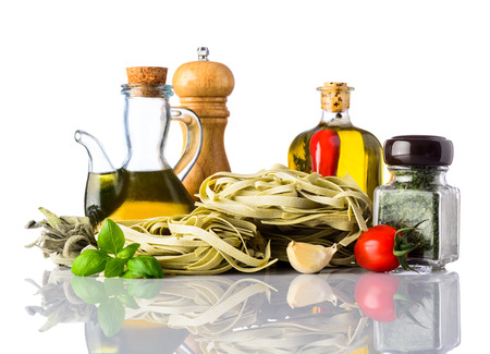 mediterranean cuisine: Green Tagliatelle Tagliolini Pasta and spices, herbs, and seasoning isolated on white background. Italian or mediterranean cuisine food.