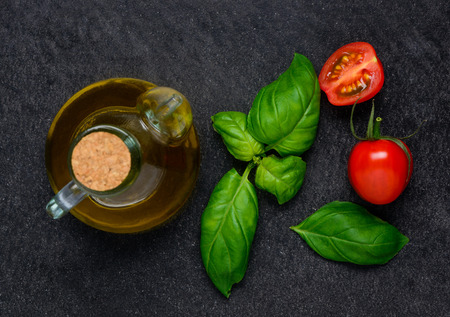 fres: Bottle of olive oil and Fresh green basil leaves with red tomato