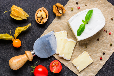 cheese knife: French Soft Camembert Cheese cut with a Cheese Knife. Nuts Tomato and peppercorn Stock Photo