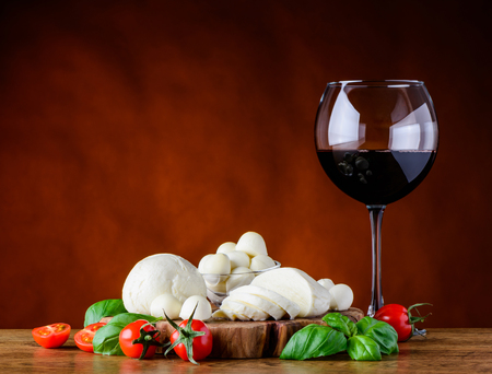 Wineglass of red wine with Juicy mozzarella cheese balls and tomato with basil