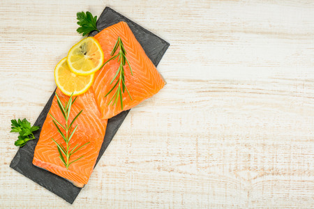 textspace: Salmon Fish Fillet with lemon and Cooking herbs on Copy space area Stock Photo