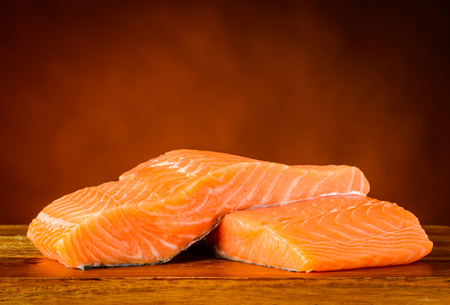 red salmon: Two slices of Red Salmon Fish Fillet on Wooden Table top.