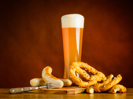 beerglass: Tall Glass Wheat beer with Grilled Sausages and Prezel. Stock Photo