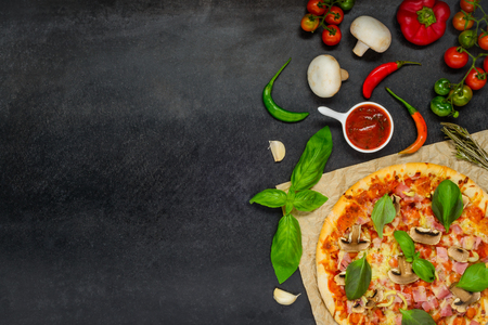 textspace: Baked Pizza with tomato sauce, cheese, mushrooms and vegetables on a dark background and Copy Space Area