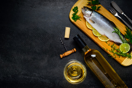 white backing: Raw Freshwater Trout Fish with White Wine in Glass and Bottle and with Copy space Text Area