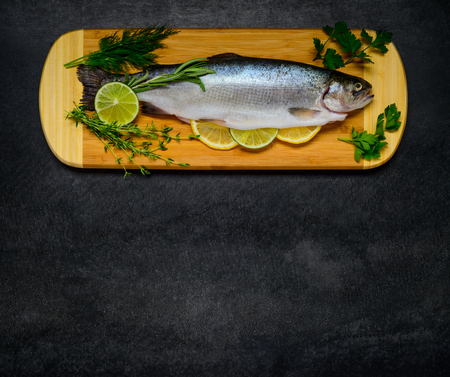 textspace: Freshwater Trout Fish ready for baking. Food Cooking ingredients on Wooden Chopping board and with Copy Space Area