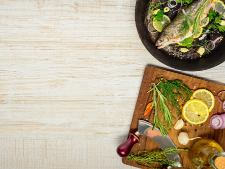 prepared fish: Prepared Fish for Cooking in frying pan and Ingredients on Wooden Chopping Board