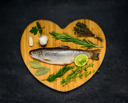 Raw Freshwater Rainbow Trout with cooking ingredients on heart shaped chopping board Stock Photo