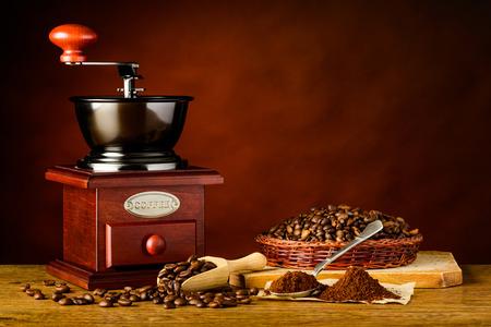 Hölzerne Hand Kaffeemühle mit Brown gerösteten Bohnen und Boden Standard-Bild