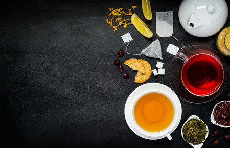 red tea: Yellow and Red Tea with white Teapot and Ingredients on Copy Space Area Stock Photo