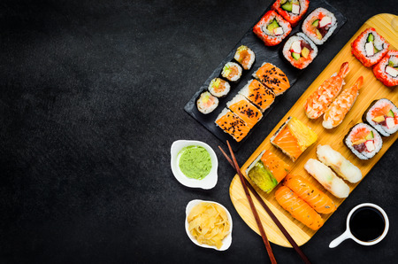 Sushi Rolls with Surimi and Smoked Fish, Wasabi and Tsukemono Ginger with Chopsticks on Copy Space Area