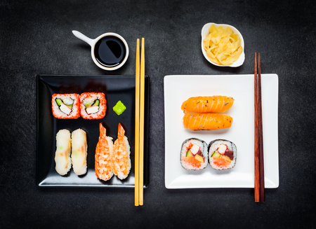 plates of food: Two Plates, Black and White with Japanese Food Sushi, Soy sauce and Ginger Stock Photo