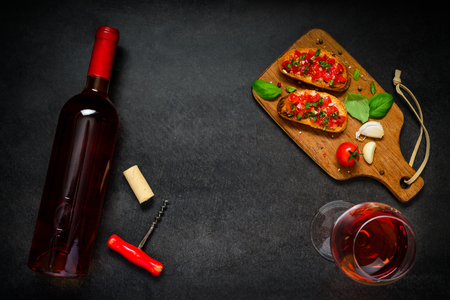 rose wine: Glass and Bottle of Rose Wine with Italian Cuisine Bruschetta Antipasto and Copy Space Text Area Stock Photo