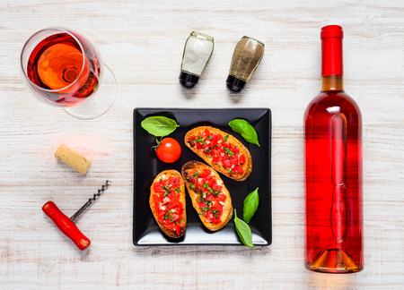 rose wine: Rose Wine in Bottle and Glass with Bruschetta Antipasto and Condiments