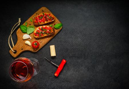 rose wine: Bruschetta Italian Cuisine Antipasto with Tomato, garlic and basil with Rose Wine on Copy Space Area