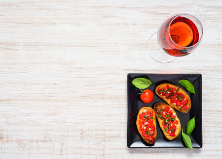 rose wine: Glass of Rose Wine with Bruschetta on Dark Plate and Copy Space Area Top View