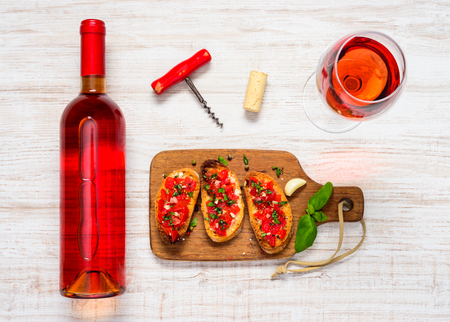 rose wine: Rose Wine in Glass and Bottle with Italian Antipasto Bruschetta and Corkscrew