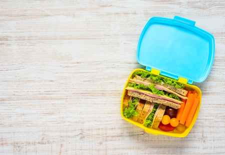 space text: Colored Lunch Box with Sandwiches and Fresh Vegetables on Copy Space Text Area Stock Photo