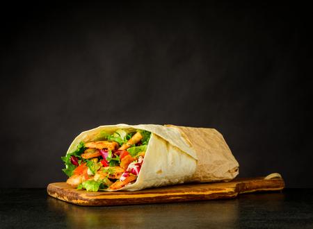 어두운 배경에 고기와 야채와 샤와 터키어 샌드위치
