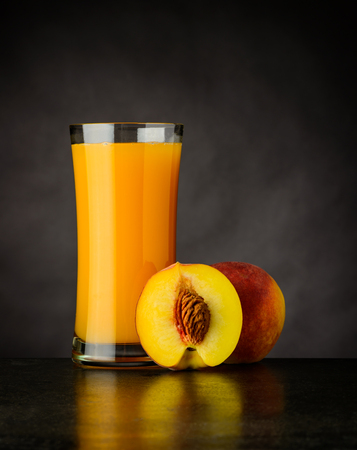 Natural, Organic and Fresh Peach Juice in Glass on Dark Background Stock Photo